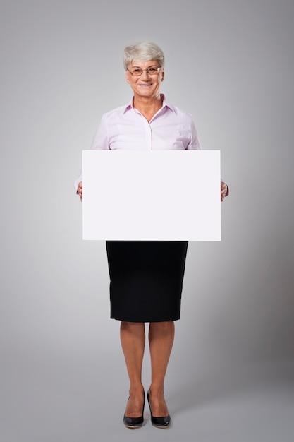 Hogere bedrijfsvrouw met leeg whiteboard Gratis Foto