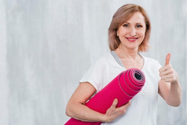 Hogere de yogamat die van de vrouwenholding thumbup gebaar tonen tegen grijze achtergrond Gratis Foto