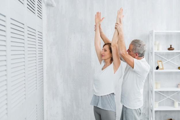 Hogere echtgenoot die zijn vrouw helpt die yogapositie doet Gratis Foto