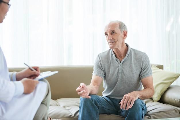 Hogere kaukasische mannelijke patiënt die gezondheidsklachten thuis delen met arts Gratis Foto