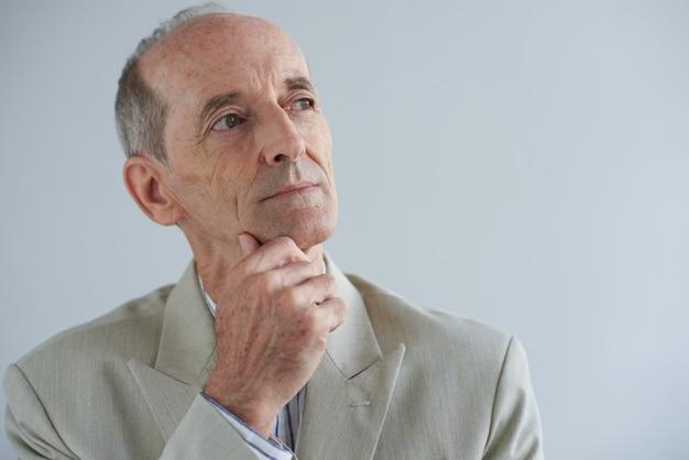 Hogere kaukasische zakenman wat betreft kin en weg kijkend met dromerig gezicht Gratis Foto