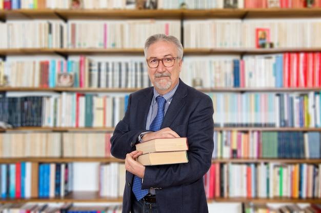 Hogere leraar die houdend een boek voor een boekenkast bevindt zich Premium Foto