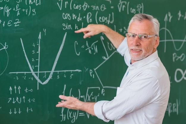Hogere leraar in glazen die wiskundevoorbeeld op groen bord verklaren Gratis Foto