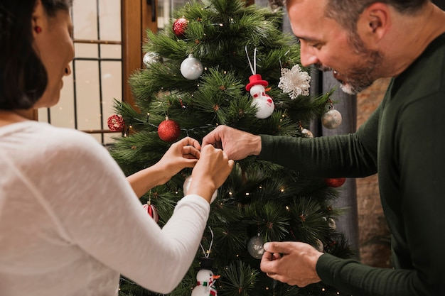 Hogere man die zijn vrouw met decoratie helpt Gratis Foto