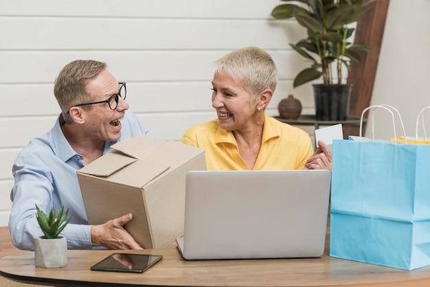 Hogere man en vrouw die hun het winkelen zakken en dozen openen Gratis Foto