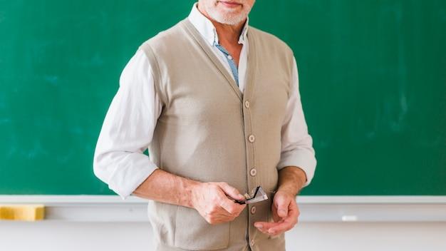 Hogere mannelijke leraar met glazen tegen bord Gratis Foto