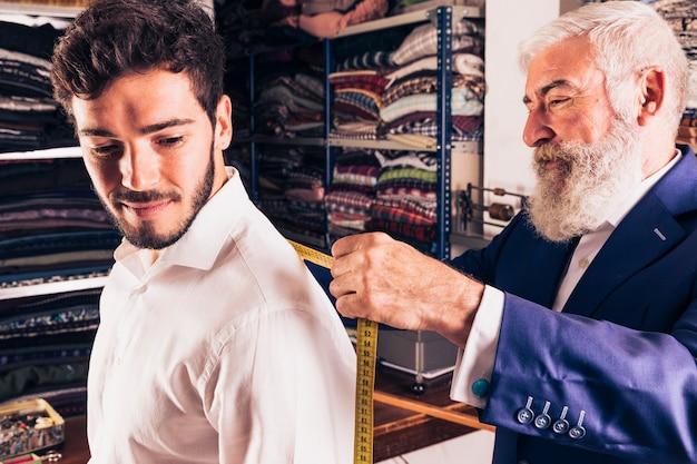Hogere mannelijke manierontwerper die meting van zijn klant in de winkel neemt Gratis Foto