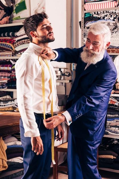 Hogere mannelijke manierontwerper die metingen van de mens in zijn winkel nemen Gratis Foto