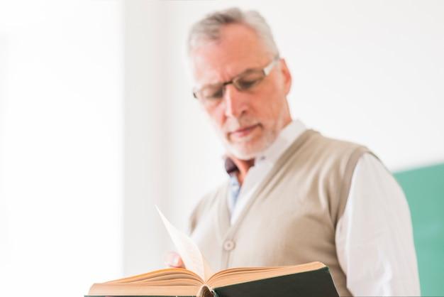 Hogere mannelijke professor in glazen die boek lezen Gratis Foto