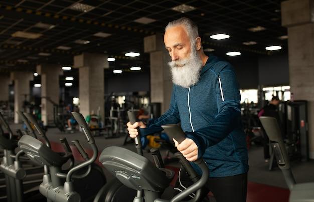 Hogere mens bij het runnen van machine in gymnastiek Premium Foto