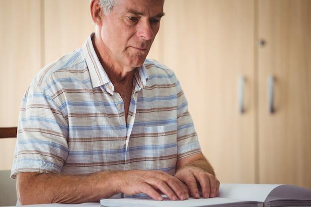 Hogere mens die braille gebruikt om te lezen Premium Foto