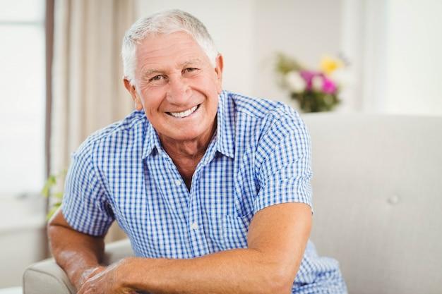 Hogere mens die camera bekijkt en in woonkamer glimlacht Premium Foto