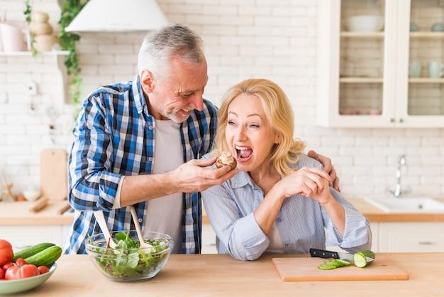 Hogere mens die de paddestoel voedt aan haar vrouw in de keuken Gratis Foto