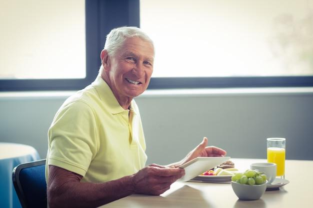 Hogere mens die digitale tablet gebruikt terwijl het hebben van ontbijt Premium Foto