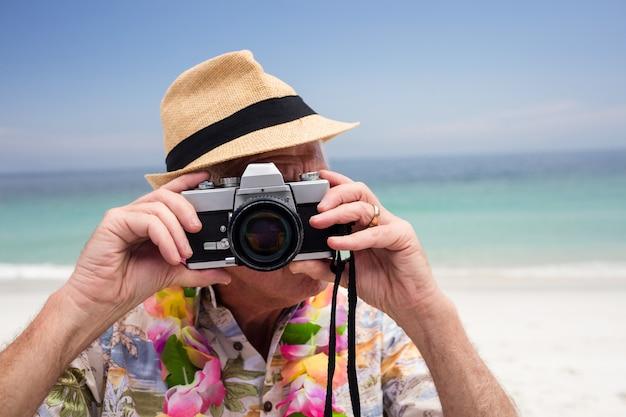 Hogere mens die een foto met camera neemt Premium Foto