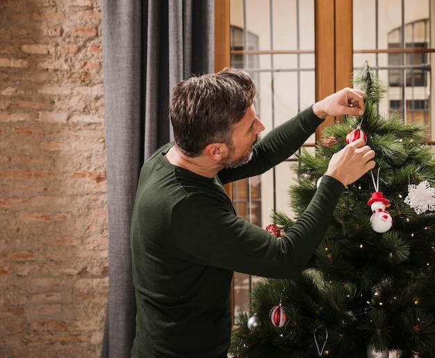 Hogere mens die kerstmisboom binnen verfraait Gratis Foto