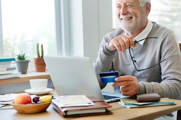 Hogere mens die online met een creditcard winkelt Gratis Foto
