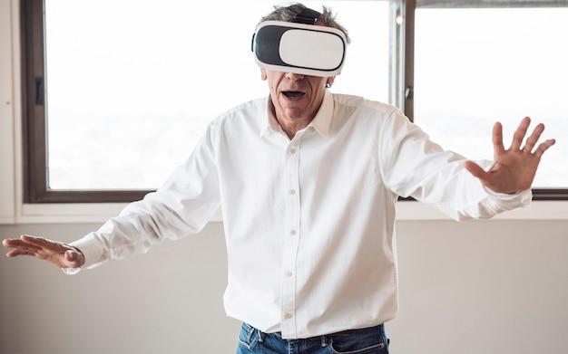 Hogere mens in wit overhemd die een virtuele werkelijkheidshoofdtelefoon in de ruimte met behulp van Gratis Foto