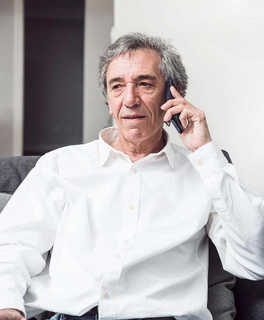 Hogere mens in wit overhemd die op mobiele telefoon spreken Gratis Foto