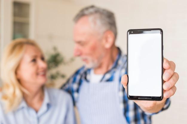 Hogere mens met zijn vrouw die mobiele telefoon naar camera toont die ter beschikking houdt Gratis Foto