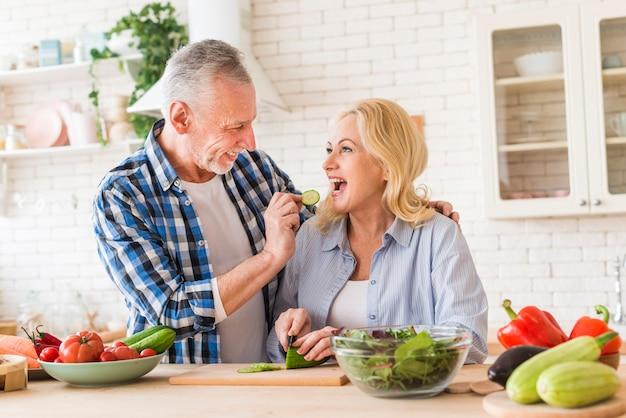 Hogere mensen voedende komkommerplak aan haar vrouw in de keuken Gratis Foto