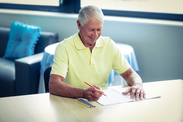 Hogere mensentekening met een kleurpotlood in tekeningsboek Premium Foto