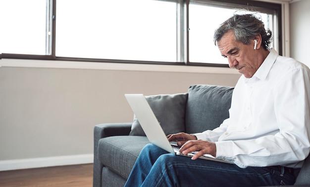 Hogere mensenzitting op bank die laptop met behulp van Gratis Foto