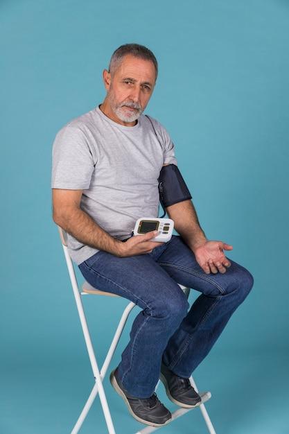 Hogere mensenzitting op stoel die bloeddruk controleren op elektrische tonometer Gratis Foto