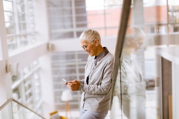 Hogere onderneemster die mobiele telefoon in modern ofice met behulp van Premium Foto