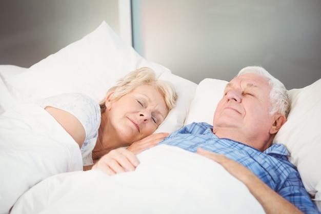 Hogere paarslaap op bed thuis Premium Foto