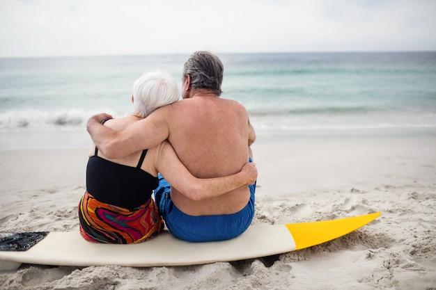 Hogere paarzitting op surfplank bij strand Premium Foto