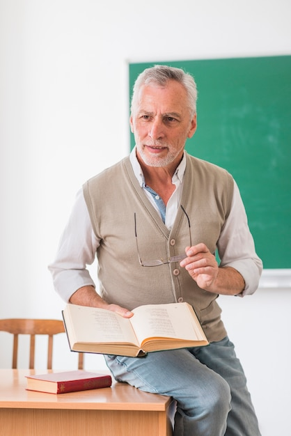 Hogere professorszitting op bureau met boek in klaslokaal Gratis Foto