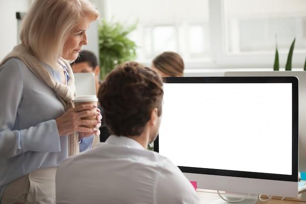 Hogere stafmedewerker die jaarlijks rapport controleert op het computerscherm die collega helpen Gratis Foto