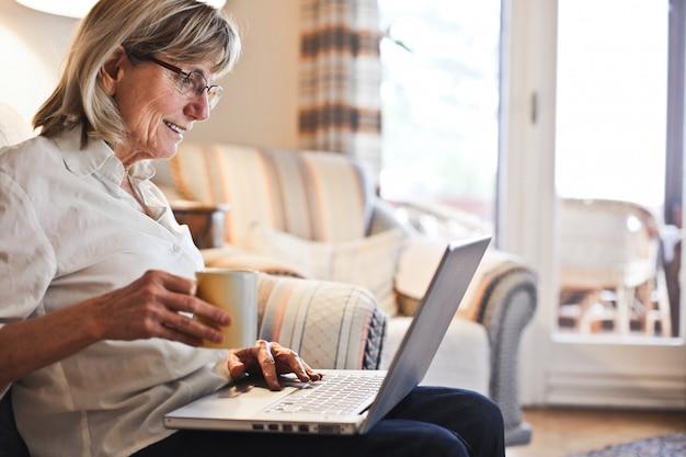 Hogere vrouw die aan laptop werkt Premium Foto