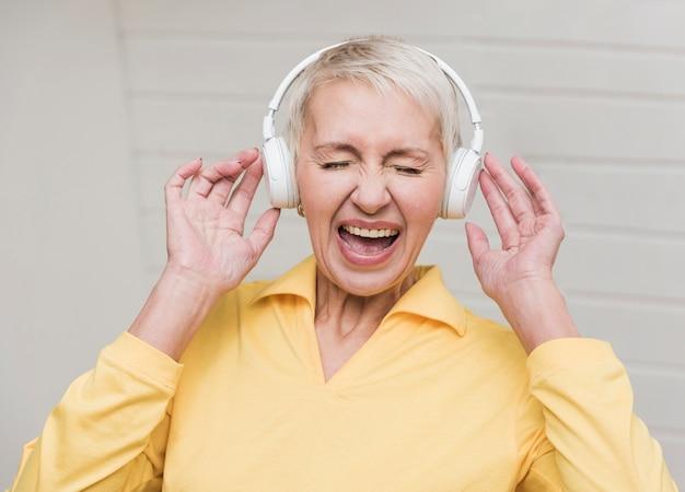 Hogere vrouw die aan luide muziek luistert Gratis Foto