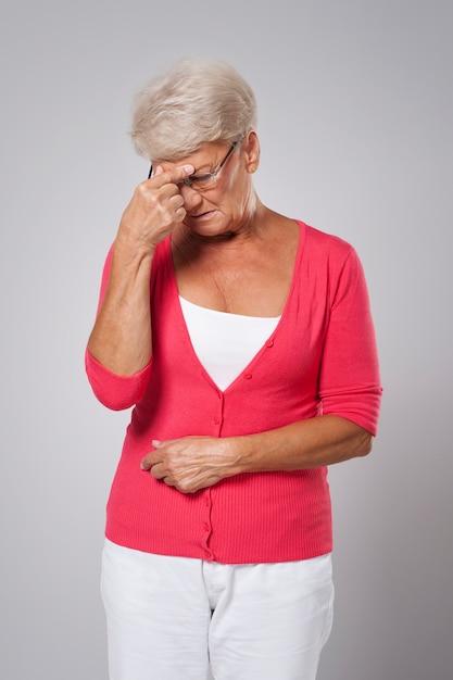 Hogere vrouw die aan sterke hoofdpijn lijdt Gratis Foto