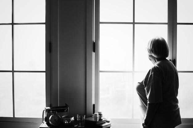 Hogere vrouw die alleen zich thuis bevindt Gratis Foto