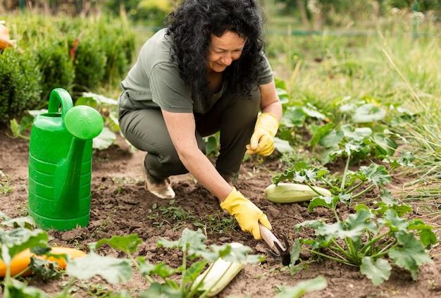 Hogere vrouw die de gewassen geeft Gratis Foto
