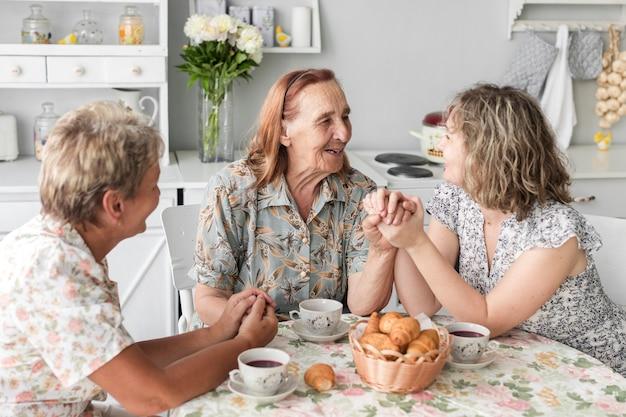 Hogere vrouw die de hand van haar dochter en van de kleindochter houden tijdens ontbijt Gratis Foto