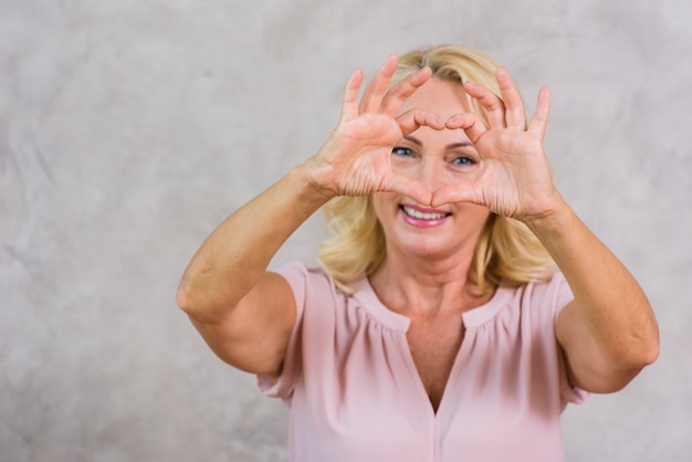 Hogere vrouw die een hart met haar vingers maakt Gratis Foto