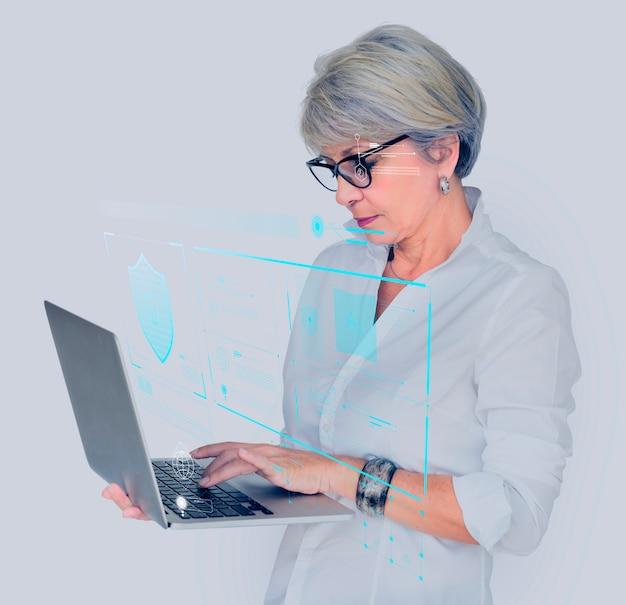 Hogere vrouw die haar tablet opent Gratis Foto