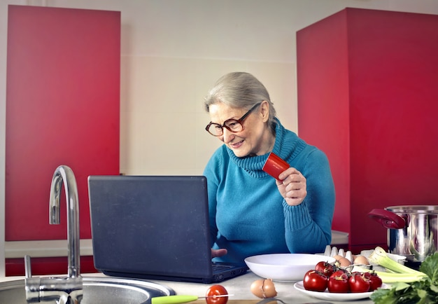 Hogere vrouw die laptop in de keuken met behulp van Premium Foto