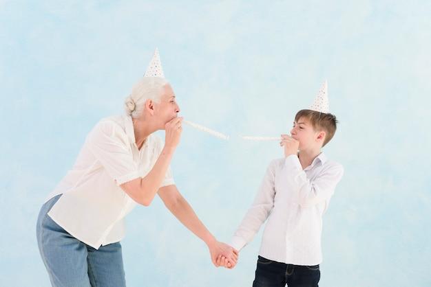 Hogere vrouw die met haar kleinzoon met partijhoed en hoorn op blauwe oppervlakte geniet van Gratis Foto