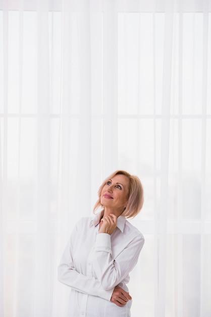Hogere vrouw die omhoog met exemplaarruimte kijkt Gratis Foto