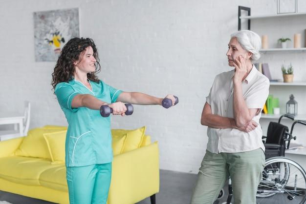 Hogere vrouw die vrouwelijke verpleegstersoefening met domoren bekijken Gratis Foto