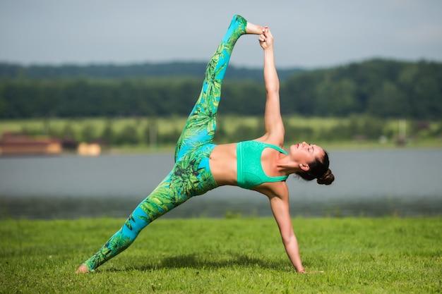 Hogere vrouw die yogaoefeningen met erachter bergen doet Gratis Foto