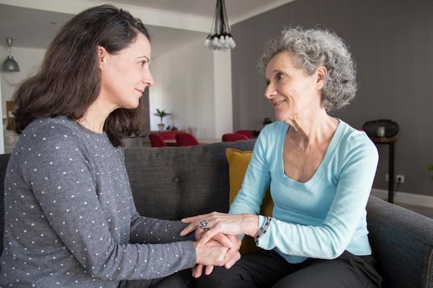 Hogere vrouw en haar dochter die en handen spreken spreken Gratis Foto