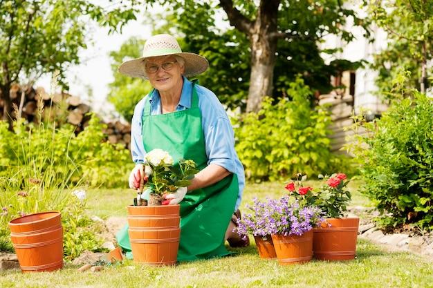 Hogere vrouw met bloemen in tuin Gratis Foto