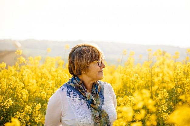 Hogere vrouw op een gebied van gele bloemen Premium Foto