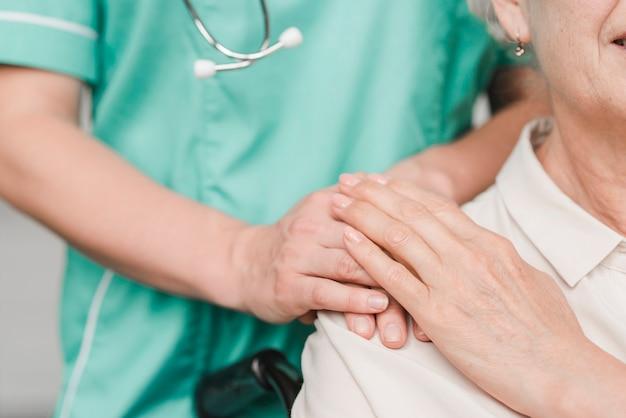 Hogere vrouwenpatiënt wat betreft vrouwelijke verpleegstershand op schouder Gratis Foto
